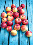 Red apples lie on a blue plank Royalty Free Stock Photos
