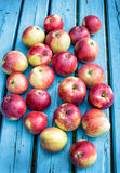 Red apples lie on blue wooden table Stock Photos