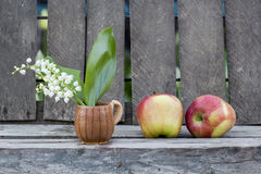 Red apples and lily of the valley flower in a ceramic small mug Stock Image