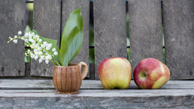 Red apples and lily of the valley flower in a ceramic small mug with wood background Royalty Free Stock Images
