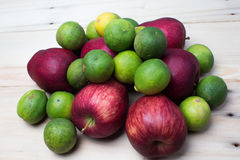 Red apples with limes. In a wooden background Royalty Free Stock Photo