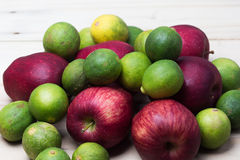 Red apples with limes. In a wooden background stock image