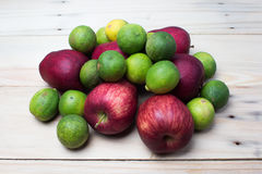 Red apples with limes. In a wooden background Royalty Free Stock Image