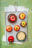 Red apples, liquid chocolate and chopped alomonds on cooling grid Royalty Free Stock Images