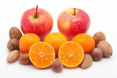 Red apples, mandarins with drops and nuts on white Royalty Free Stock Photo