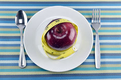 Red apples, measuring tape and Flatware in dish on napery. Royalty Free Stock Images