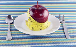 Red apples, measuring tape and Flatware in dish on napery. Royalty Free Stock Image