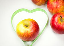 Red apples with measuring tape forming a heart shape Stock Photos