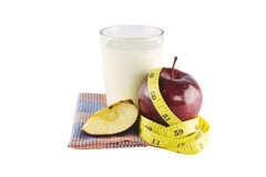 Red apples, measuring tape, glass of milk, tomato and fabric iso Royalty Free Stock Photography