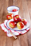 Red apples in a metal plate on wooden background. Red organic apples in a metal plate on a rustic wooden background stock photos