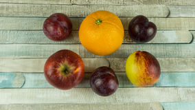 Red apples, nectarine, blue plums and orange Stock Image