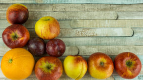 Red apples, nectarine, blue plums and orange Stock Photo