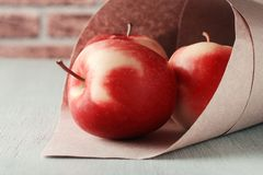 Red apples in a paper bag. On a wooden table, bright, delicious, positive still life royalty free stock photography