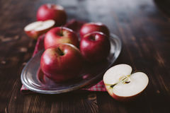 Red apples on plank wooden table. Metal plate Royalty Free Stock Photos