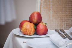 Red apples in a plate on white table, Royalty Free Stock Photos