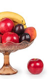 Red apples, plums, bananas and peaches in a glass vase Stock Photo