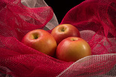 Red apples on a red background. In a photographic studio Stock Photo
