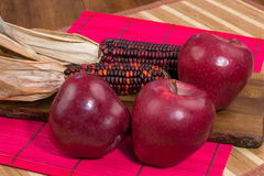 Red apples, red corn, red surface on wood Stock Photography