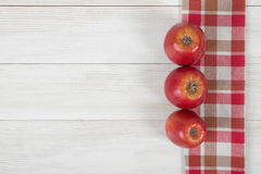 Red apples are in row on wooden surface with checkered kitchen tablecloth. Top view. Red apples are in a row on a wooden surface with checkered kitchen Royalty Free Stock Photo