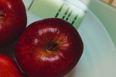 Weight loss concept. Health vegetarian food.macros shot food concept. Red apples on a scale. Macro shot. Vegetarian healthy food Royalty Free Stock Images