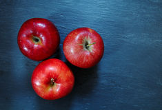 Red apples. Red apples on slate board. Three red apples. Eating fresh apples royalty free stock images
