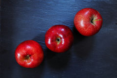 Red apples. Red apples on slate board. Three red apples. Eating fresh apples stock photo