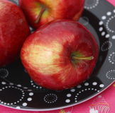 Red apples. Some red apples on a black plate royalty free stock photography