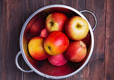 Red apples in a strainer on the wooden table Stock Photos