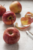 Red apples on the table. Four red apples and a knife on the white wooden table royalty free stock photography