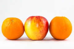 Red apples with two orange. Horizontal line of red apples with two orange stock images