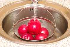 Red apples under current water. Red apples in sieve in kitchen-sink under stream water Stock Photography