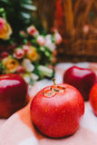 Red apples and wedding rings on a plaid blanket near the basket Royalty Free Stock Image