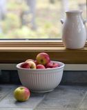 Red Apples in a White Bowl 0293A. Red apples in a white ceramic bowl sitting on a slate gray tiled counter.  A White pitcher sits in teh background on a wooden Royalty Free Stock Photo