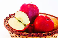 Red apples. Whole and cut, in a wicker basket Royalty Free Stock Photo