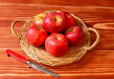 Red apples on a wicker plate with a knife Stock Photography