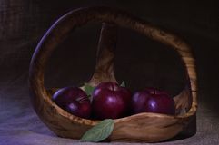 Red apples in wooden basket with few green leaves on natural sac. Composition with three red apples in wooden basket decorated by few green leaves on rough Stock Images