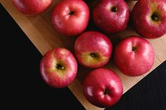 Red apples on a wooden Board on a dark background. The concept of organic healthy foods royalty free stock images