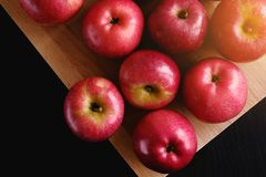 Red apples on a wooden Board on a dark background. The concept of vegetarian food, organic products stock image