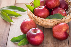 Red apples on wooden table and basket Stock Photography