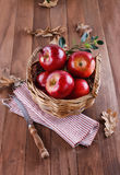 Red apples in a woven basket on wooden background Royalty Free Stock Photos