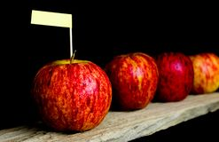 Red apples and yollow label put on wooden with black background Stock Photography