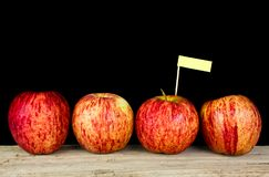 Red apples and yollow label put on wooden with black background Royalty Free Stock Photos