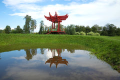 Red arbor in Japanese style on the shore of a pond. Park Marino. Leningrad region, Russia. Red arbor in Japanese style on the shore of a pond. Park Marino Stock Images