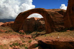 Red arch against a blue sky and white clouds. A beautiful red arch (Rainbow Bridge) is set against a bright blue sky with a large bank of white clouds blowing in Stock Photos