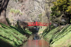 Red arched bridge over stream in botanical gardens Royalty Free Stock Photos