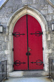 Red arched doors, black ironwork, stone church, Keene, New Hamps Stock Photography