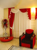 Red armchair. And curtain and decorative red flowers in corner Stock Images