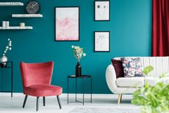 Red armchair in living room. Red armchair, white sofa, paintings and black table in a green living room interior royalty free stock photography