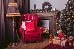 Red armchair in a modern style in the New Year`s retro interior with a Christmas tree, a fireplace and gift boxes. Red armchair in modern style in the New Year`s Royalty Free Stock Photography