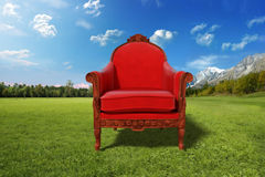 Red armchair in the nature. Very high resolution 3D rendering of a red armchair in a grass field Royalty Free Stock Images